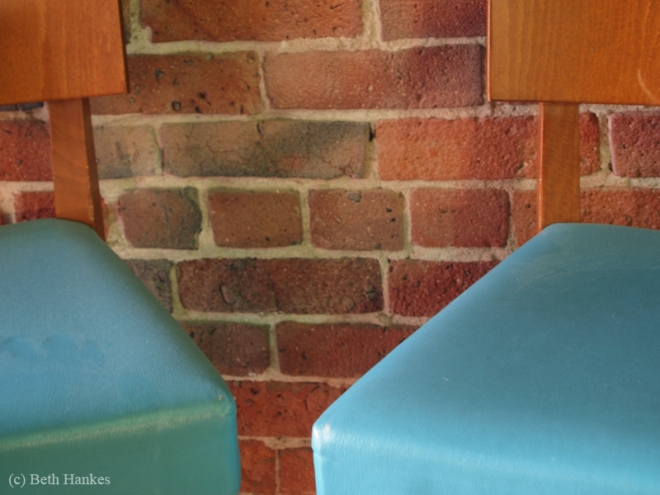 two vintage chairs in front of a brick wall