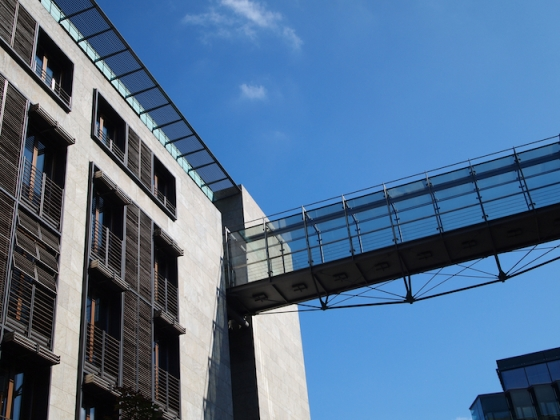 A bridge connects two government buildings, high above the street.